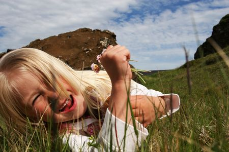 A cute little blond girl lying in the grass under a partly cloudy sky with flowers