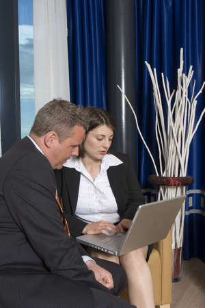 A businessman an businesswoman smartly dressed, having a conversation and working on a project in a laptop Stock Photo