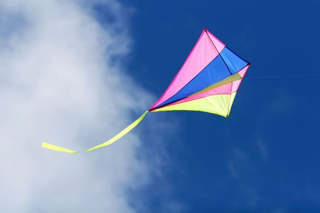 a kite flying against a blue sky in sunlight, bright colors and streaming tail