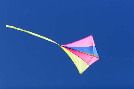 flying a kite: a kite flying against a blue sky in sunlight, bright colors and streaming tail