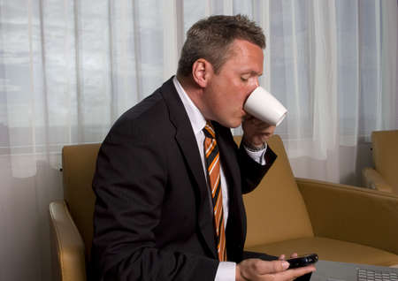 scrutiny: A man in shirt and tie reading a email and drinking coffee