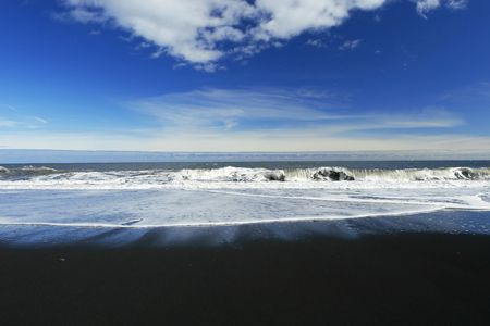 german north sea region: waves crashing on a sandy black beach , deep blue sky and clouds in background