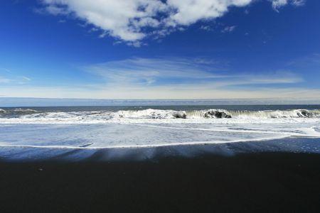 german north sea region: waves crashing on a sandy black beach , deep blue sky and clouds in background