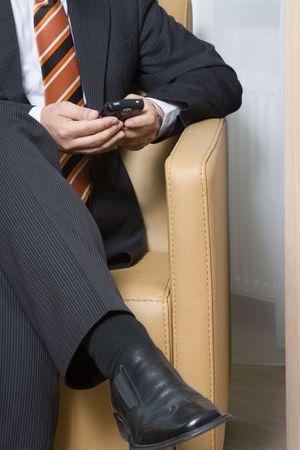 그의 휴대 전화에 의자 문자 메시지에 앉아 사업가 스톡 콘텐츠