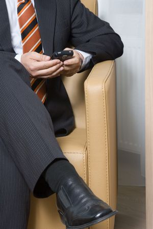Businessman sitting in chair texting on his mobile phone