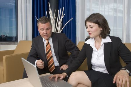 A businessman an businesswoman smartly dressed working on a business deal on a laptop Stock Photo - 1195035