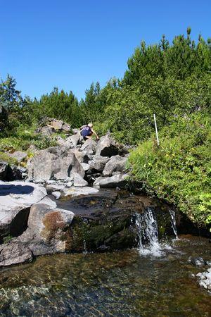 young boy climbing over rocks in a mountain spring photo