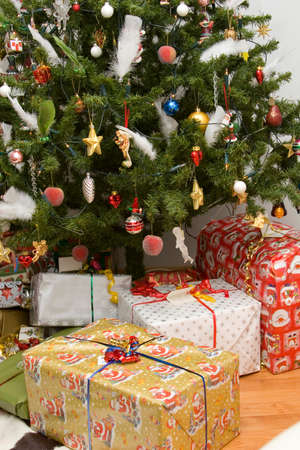 christmas presents lying under a decorated christmas tree