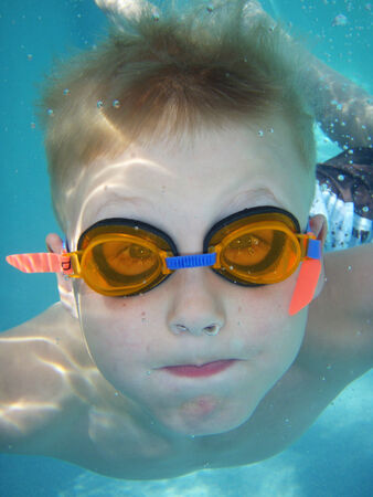 Young boy diving, shot underwater, boy looking straight at camera