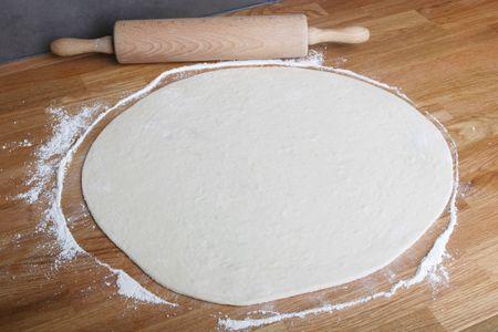 masa: pizza casera en cocina de madera con rodillo