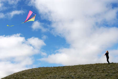 Young boy on a hill flying his kite