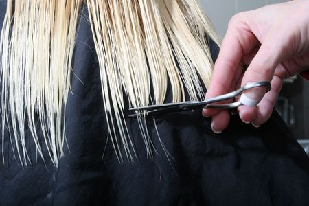 styling: long blond hair being cut