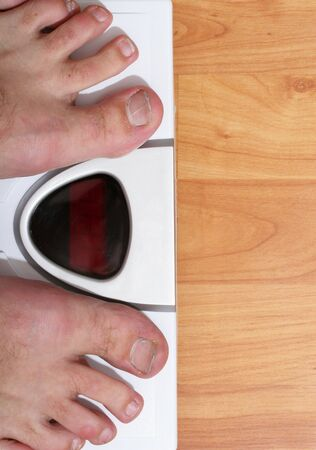Man standing on a digital scale Stock Photo