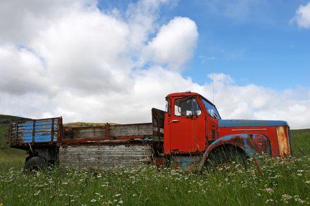 Broken down vintage truck standing in a field of grass in summer photo