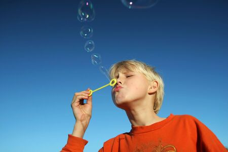 small boy blowing bubbles agains a deep blue sky photo