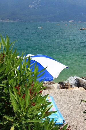 matress: A beach umbrella on a beach at lake garda, colorful inflateable matress on the sand, fantastic holiday or vacation image,