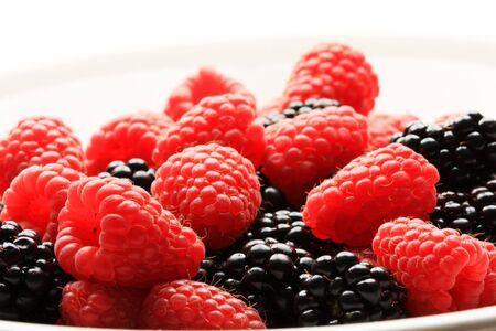 A bowl of raspberries and blackberries, shot in studio photo