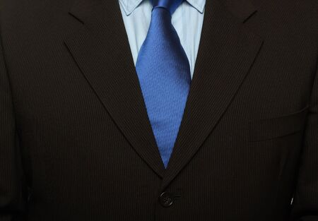 cropped shot of torso part of a man in black suit and blue tie Stock Photo