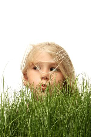 A little blonde girl peeking up over green grass, isolated on white