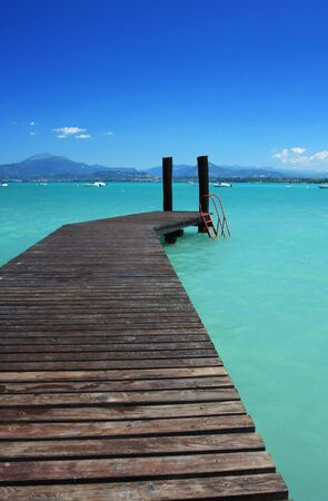 garda: a small jetty in lake Garda Italy, fantastic color in the water and sky. Perfect for concepts of vacation or holidays