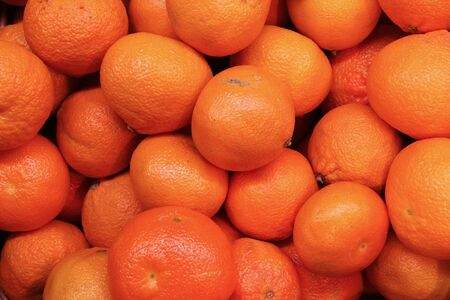 citrus reticulata: frame filling shot of clementines at a farmers market,great detail, fantastic for your designs