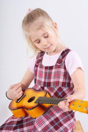 letras musicales: peque�a ni�a tocando una guitarra de juguete Foto de archivo