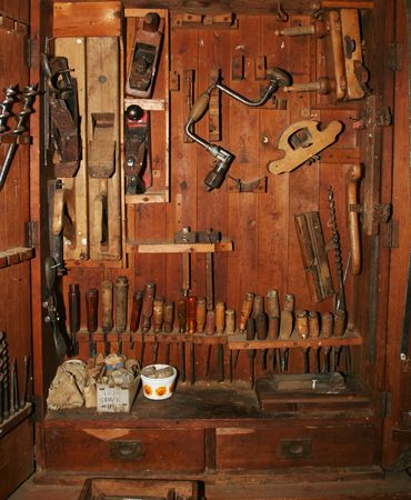 cupboard: Very old and worn woodworking tools in worn down cabinet Stock Photo