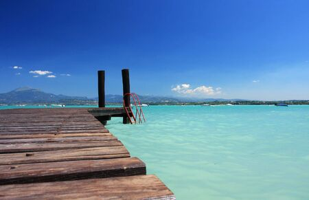 a small jetty in lake Garda Italy, fantastic color in the water and sky. Perfect for concepts of vacation or holidays