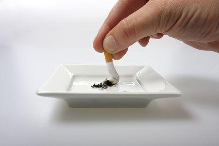 흰색에 고립 된 흰색 재떨이에 담배를 손으로 스텁