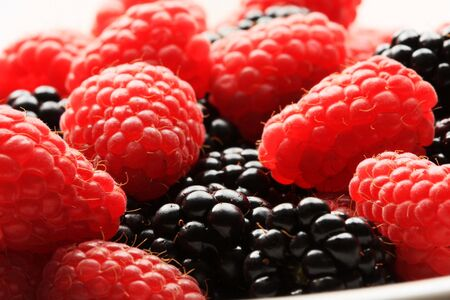 lighthing: Red raspberries and blackberries in a bowl, lighting from behind to create high contrast. great for concepts of freshness and desserts Stock Photo