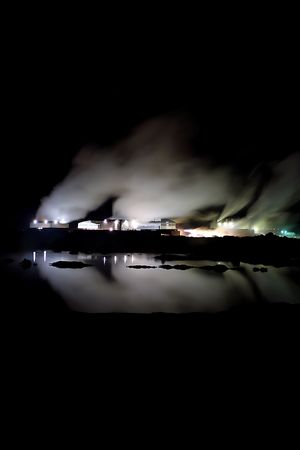 Geothermal powerplant in Iceland producing clean renewable energy, taken at night, steam columns lighted up and reflected in water. Stock Photo