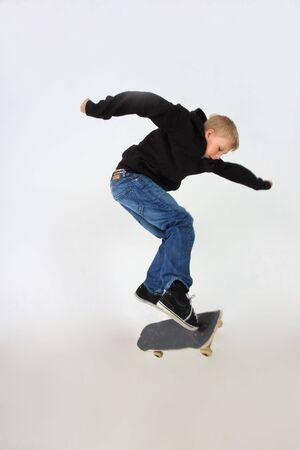 Skateboarder doing a kickflip with his board, Shot in studion and isolated on white Stock Photo