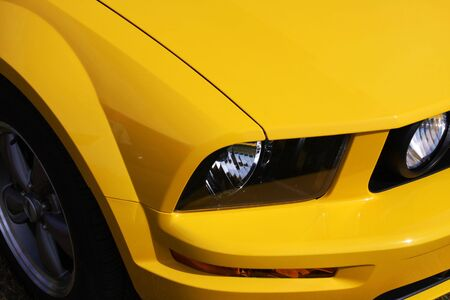 paintjob: part of front end of a yellow sportscar, headlights and part of wheel showing
