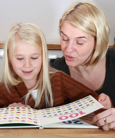 home schooling: mother and daughter having fun learning numbers and reading
