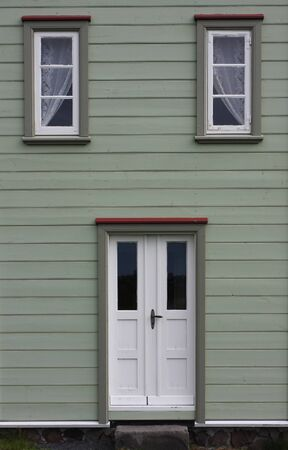 green painted front on a wooden house, doorway and windows form a sort of a face