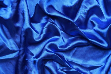 creases: Blue colored satin shot from above with creases and folds creating all sorts of shapes and shadows