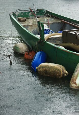 A dirty fishing boat floating on water in heavy rain photo