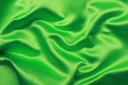 creases: Green colored satin shot from above with creases and folds creating all sorts of shapes and shadows