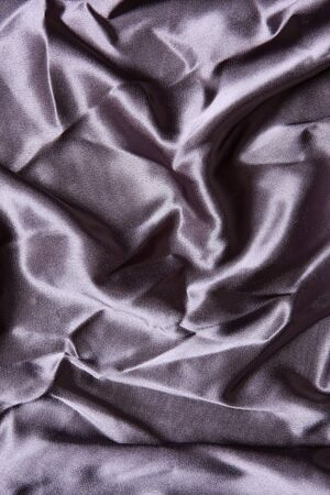 Grey colored satin shot from above with creases and folds creating all sorts of shapes and shadows photo