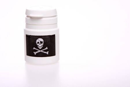 pillbox:  White pillbox isolated on white with copy space, Black label with skull and bones on the pillbox Stock Photo