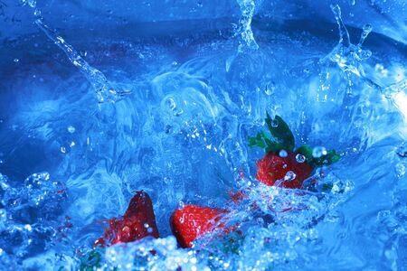 deliberately: Fresh strawberries splashing into cold water, white balance deliberately set to custom to create feeling of cold and fresh. Stock Photo