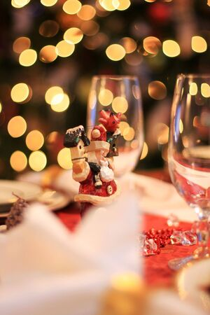 santa clause decoration on a table set for christmas dinner, christmas lights on the tree blurry in background Stock Photo - 6827533