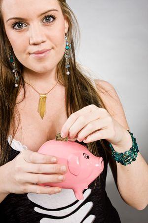 mujer bonita: mujer bonita joven que pone el dinero en una alcanc�a de color rosa