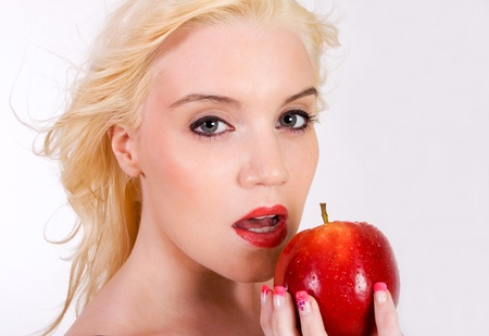 seductive women: A very sexy and sensual young woman holding a red apple about to bite into it. Shot on white with copy space