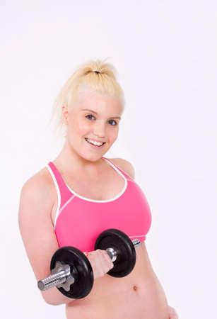 levantando pesas: mujer joven con una gran figura sonriendo a la cámara, mientras que el levantamiento de pesas.