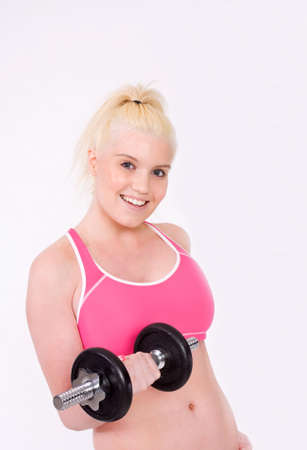 Young woman with a great figure smiling at camera while lifting weights. Stock Photo