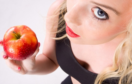 voluptuous women: pretty young woman holding a red apple shot from above looking up at camera.
