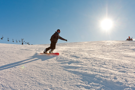 wintersport: Teenager enjoying snowboarding in perfect conditions