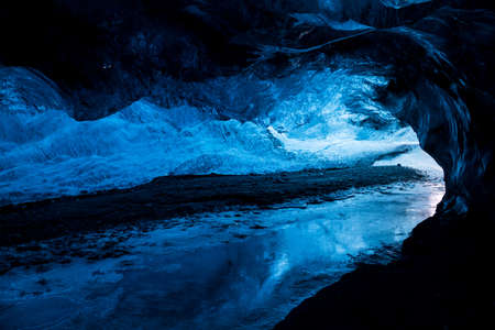 silhoutted: Inside an icecave in Vatnajokull, Iceland  A climber silhoutted against the ice  The ice is thousands of years old and so packed it is harder than steel and crystal clear  These caves are formed by meltwater that rushes from over and underneath the glacie