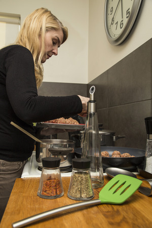 dinnertime: Woman preparing dinner in a home kitchen Stock Photo